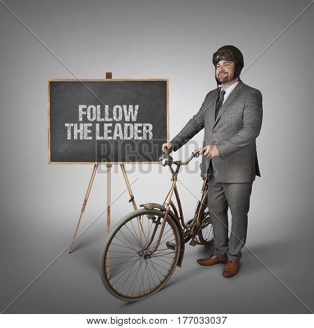 Follow the leader text on blackboard with businessman and vintage bike