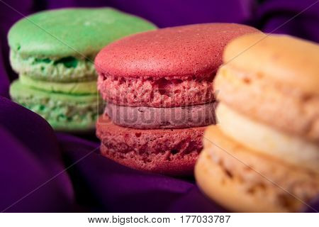 Three Colorful Macaroons On Purple Background. French Dessert. Close Up. Macro.