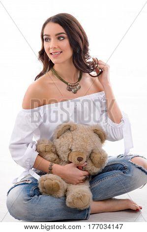studio Portrait of gorgeous woman model with Teddy bear wearing beautiful jewellery