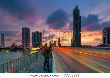Sunset scence of Bangkok Panorama View of Taksin bridge in Bangkok city with sunset sky and clouds at Bangkok Thailand. And Car light on road. Photographer is taking photo