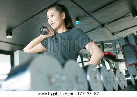 Women Exercising With Metal Dumbbells In Modern Gym