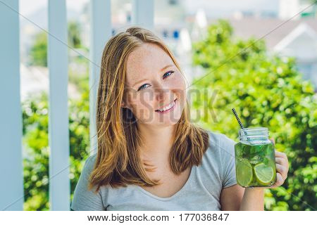 A Young Woman Holds A Mason Jar In Her Hand With A Mojito. Spring Drink Concept