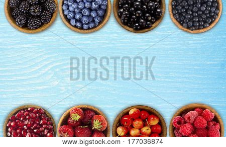 Black blue and red berries. Blackberries blueberries currants blueberries strawberries pomegranate; cherries in a wooden bowls. Berries at border of image with copy space for text. Top view.