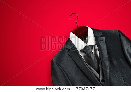 Men´s elegant grey suit and white shirt on a red velvet clothes hanger in bottom right corner on red background.