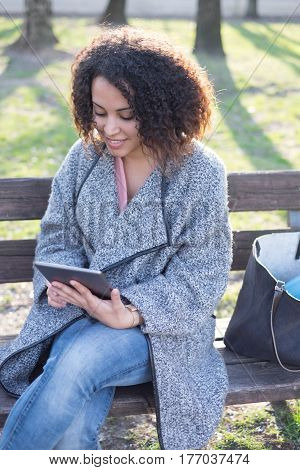 Black Woman Using App On Tablet Seated Bench