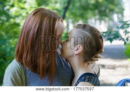 Two young women looking at each other with the passion. Horizontal outdoors shot.