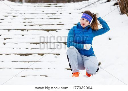 Outdoor sport exercises sporty outfit ideas. Woman wearing warm sportswear getting ready before exercising outside during winter.