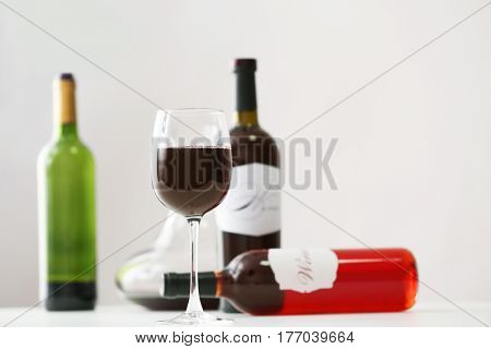 Table with wineglass and bottles of red wine on light background