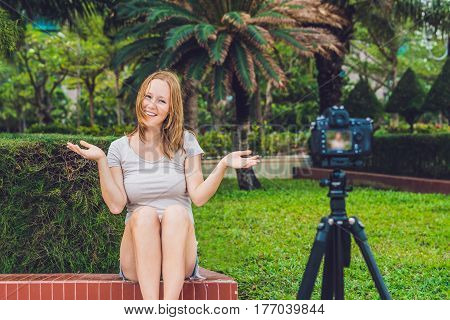 A Young Female Blogger Is Leading Her Video Blog In Front Of The Camera In The Park. Blogger Concept