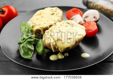 Portion of delicious baked potato with cheese sauce