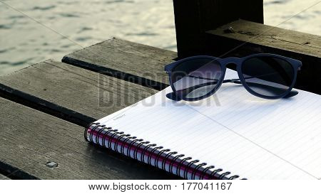 Sunglasses and white memo notebook on the wood