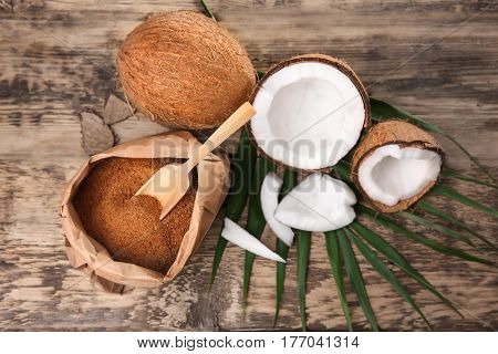 Paper pack of brown sugar and coconut on wooden background
