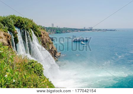 Beautiful view of the waterfall, falling into the Mediterranean sea from a high cliff on the background of blue sky and pleasure craft