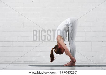 Beautiful young woman wearing white sportswear doing yoga on the background of white wall.