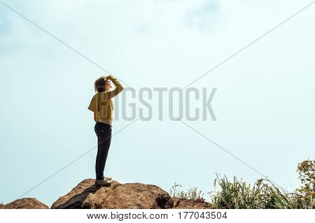 Female hiker is standing on the edge of abyss above vast forest territory of foggy mountains in Sri Lanka. Adventure of young beautiful woman