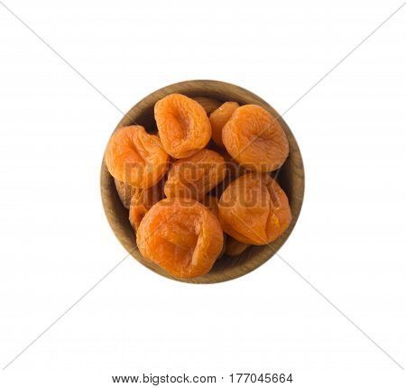 Dried apricots in a wooden bowl. Dried fruit with copy space for text. Top view. Apricots isolated on white background