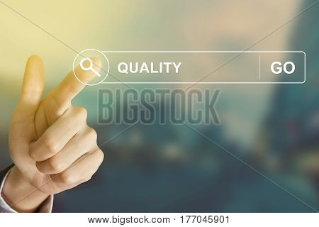 business hand clicking quality button on search toolbar with vintage style effect