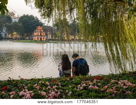 Portrait of a unidentified lovely couple looking at Turtle tower in the center of Hoan kiem lake sunset