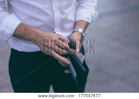 Man standing holding black wallet and picking up a money