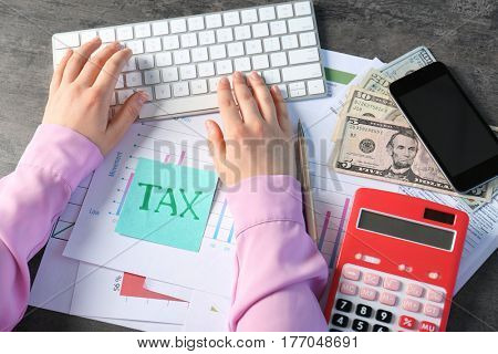 Female hands working with individual income tax return form while typing on keyboard