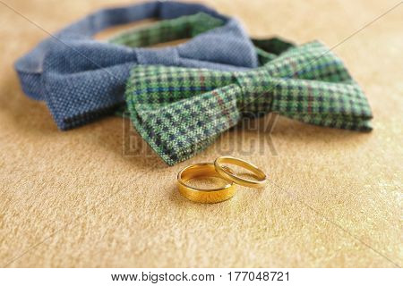 Wedding rings and bow ties on table