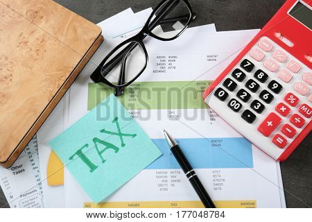 Calculator with documents, glasses and stationery on table. Tax concept