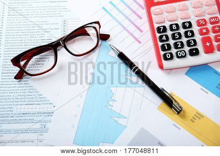 Calculator with glasses and pen on documents. Tax concept