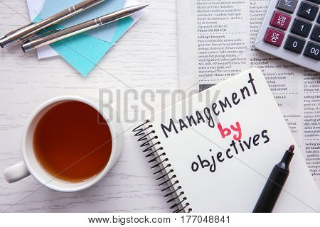 Notebook with written text MANAGEMENT BY OBJECTIVES on wooden background