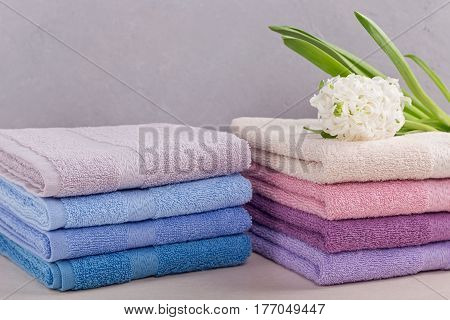 Two stacks of colorful bath towels with hyacinth flower on light background. Pastel colors cotton or bamboo towels. Hygiene fabricspa and textile concept
