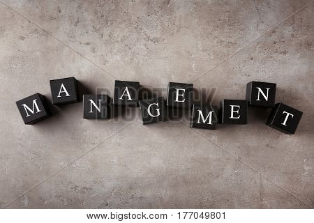 Wooden cubes with word MANAGEMENT on color background