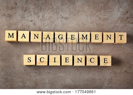 Wooden cubes with text MANAGEMENT SCIENCE on color background