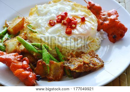 spicy stir fried crispy pork curry with egg and roasted pork stick