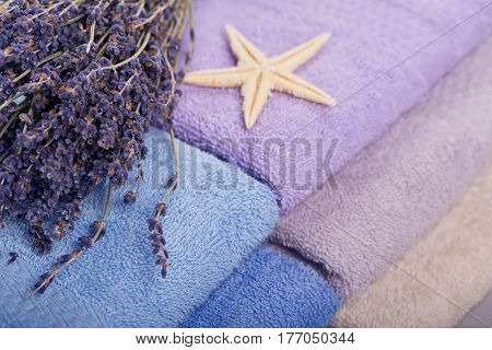 Stack of colorful bath towels with bouquet of lavender flowers and sea stars on light background. Pastel colors cotton towels. Hygiene fabricspa and textile concept. Close up