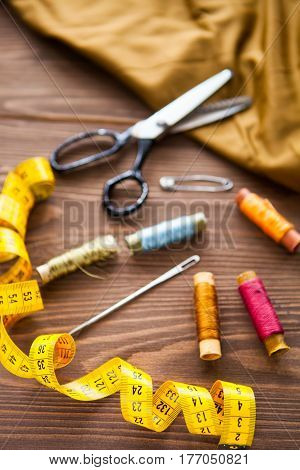 Tailoring. Tape measure and colorful thread on dark wooden background flat lay. Set
