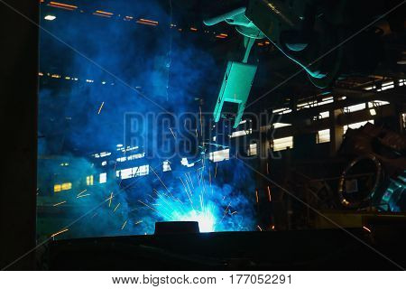 Sparks and smoke from robot welding in manufacturing