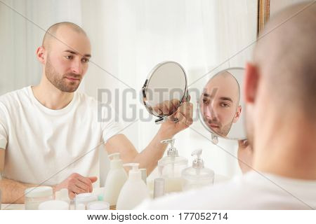 Hair loss concept. Young handsome man looking at mirror