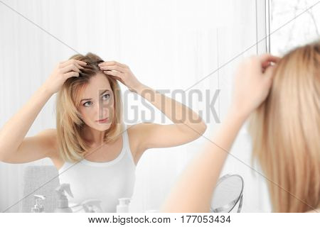 Young woman with hair loss problem looking in mirror at home