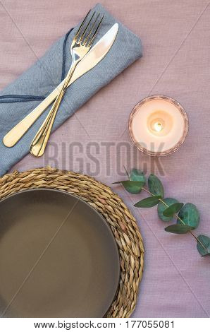 Elegant table setting on purple linen cloth dark plate rattan coaster cutlery blue napkin burning candle twig of silver dollar eucalyptus top view flatlay