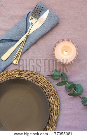 Elegant table setting on purple linen cloth dark plate rattan coaster cutlery blue napkin burning candle twig of silver dollar eucalyptus top view flatlay