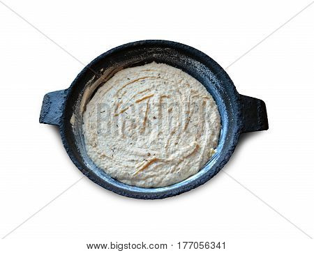 Dough with caraway seeds in a buttered frying pan