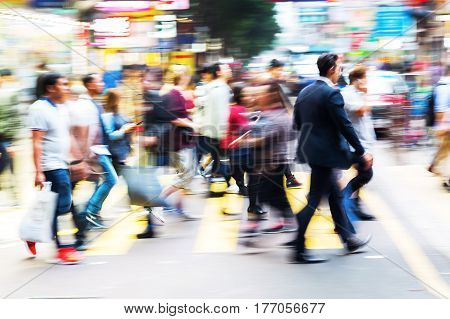 picture with motion blur of a crowd of people crossing a street in Hongkong poster