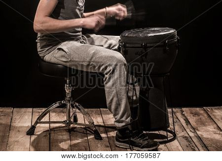 Man Playing A Djembe Drum And Cymbals On A Black Background