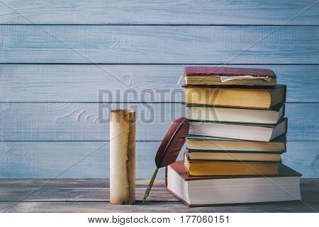Literature concept. Brown feather near old scroll and stack of old books against blue wooden background.