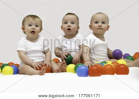 2 toddler boys and an infant girl playing with bright toys. Horizontal family studio shot