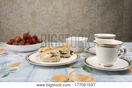 Image of scones with jam, tea and strawberries on a table