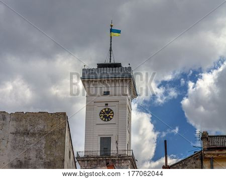 Ukrainian flag at the top of Lviv city hall clock tower Ukraine with a cloudy background