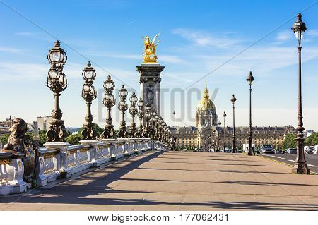 Pont Alexandre III bridge over river Seine and Hotel des Invalides in the background in the sunny summer morning. Bridge decorated with ornate Art Nouveau lamps and sculptures.