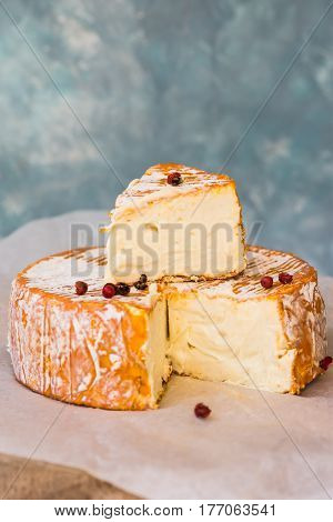 Soft cheese camambert with orange rind cut off slice red pepper corns on waxed paper close up creamy texture