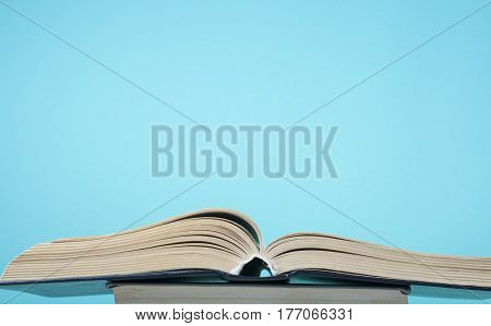 Open book, hardback books on blue background.. Back to school. Copy space for text.