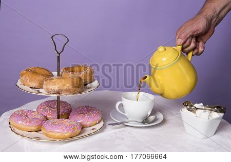 Unrecognisable hand pouring a cup of tea at a table with doughnuts